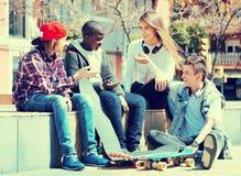 Gruppe entspannende und plaudernde Jugendfreunde Lizenzfreie Stockfotos