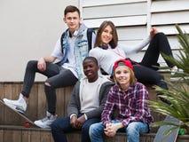 Gruppe entspannende und plaudernde Jugendfreunde Stockfotografie