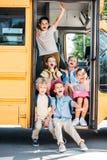 Gruppe entzückende Schulkinder, die auf Treppe des Schulbusses sitzen stockfotos