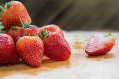 Gruppe Erdbeeren auf Holztisch, mit hellen Strahlen Stockbilder