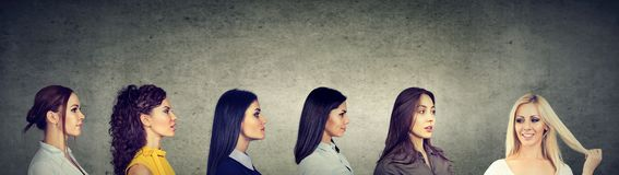 Gruppe ernste Frauen des Brunette, die ein glückliches blondes Mädchen betrachten Lizenzfreies Stockbild
