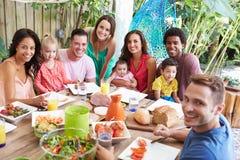 Gruppe Familien, die zu Hause Mahlzeit im Freien genießen Stockbilder