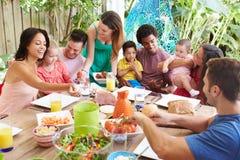 Gruppe Familien, die zu Hause Mahlzeit im Freien genießen lizenzfreie stockfotografie