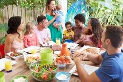 Gruppe Familien, die zu Hause Mahlzeit im Freien genießen lizenzfreie stockbilder