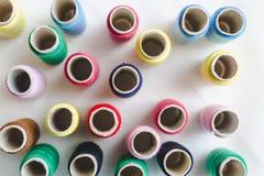 Gruppe farbige Fadenspulen auf weißem Baumwollstoff, Draufsicht lizenzfreie stockfotos