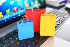Gruppe Farbpapiereinkaufstaschen auf Laptoptastatur Lizenzfreies Stockfoto
