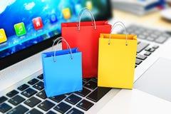 Gruppe Farbpapiereinkaufstaschen auf Laptoptastatur Lizenzfreie Stockfotografie
