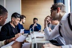 Gruppe fokussierte die männlichen Geschäftsleute, die um Computer bei der Bürounterhaltung erfasst wurden stockbilder