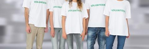 Gruppe freiwillige Leute, die zusammen mit unscharfem Hintergrund stehen Stockbilder
