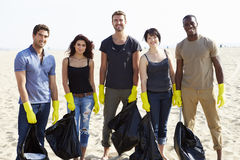 Gruppe Freiwilligen, die Abfall auf Strand aufräumen stockfotos
