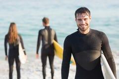 Gruppe Freunde auf Wetsuits mit einem Surfbrett an einem sonnigen Tag Lizenzfreies Stockbild