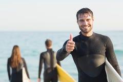 Gruppe Freunde auf Wetsuits mit einem Surfbrett an einem sonnigen Tag Stockbild