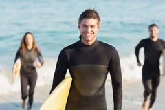 Gruppe Freunde auf Wetsuits mit einem Surfbrett an einem sonnigen Tag Lizenzfreie Stockfotografie