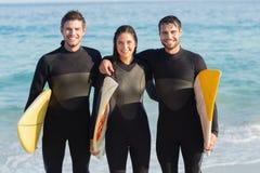 Gruppe Freunde auf Wetsuits mit einem Surfbrett an einem sonnigen Tag Lizenzfreie Stockbilder