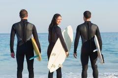 Gruppe Freunde auf Wetsuits mit einem Surfbrett an einem sonnigen Tag Stockbilder