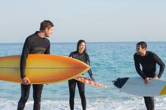 Gruppe Freunde auf Wetsuits mit einem Surfbrett an einem sonnigen Tag Stockfoto