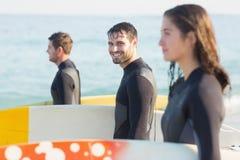 Gruppe Freunde auf Wetsuits mit einem Surfbrett an einem sonnigen Tag Lizenzfreie Stockfotos