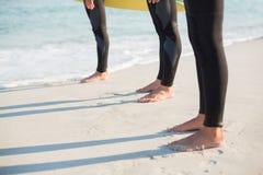 Gruppe Freunde auf Wetsuits mit einem Surfbrett an einem sonnigen Tag Stockfotos
