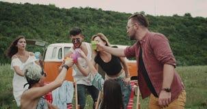 Gruppe Freunde am charismatischen Beifall des Picknicks sehr mit den bunten Gläsern, mitten in Feld, Hintergrund stock video