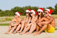 Gruppe Freunde in den Sankt-Helferhüten auf Strand Stockfoto