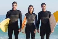 Gruppe Freunde in den Wetsuits mit einem Surfbrett an einem sonnigen Tag Lizenzfreie Stockfotografie