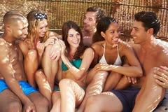 Gruppe Freunde in der Badebekleidung, die sich draußen zusammen entspannt Stockfotografie