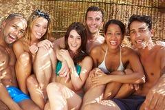 Gruppe Freunde in der Badebekleidung, die sich draußen zusammen entspannt Lizenzfreie Stockbilder