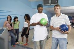 Gruppe Freunde an der Bowlingbahn Stockfotos