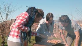 Gruppe Freunde der jungen Leute grillen shashlik Fleisch auf Holzkohlengrill auf Hinterhof Zusammen sprechen und lächeln