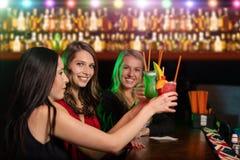 Gruppe Freunde an der Stange, die ihr Glas von anhebt Stockfotografie