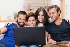 Gruppe Freunde, die über einen Laptop lachen Stockbild