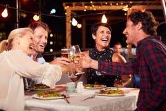 Gruppe Freunde, die Abendessen am Dachspitzenrestaurant essen lizenzfreie stockfotos