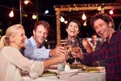 Gruppe Freunde, die Abendessen am Dachspitzenrestaurant essen stockbild