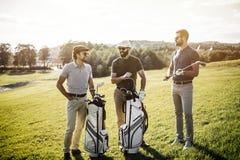 Gruppe Freunde, die auf den Golfplatz gehen lizenzfreie stockfotografie