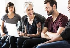 Gruppe Freunde, die auf der Couch sitzen lizenzfreies stockfoto