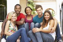 Gruppe Freunde, die auf Jobstepps des Gebäudes sitzen Lizenzfreie Stockfotos