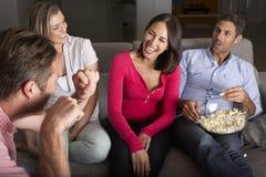 Gruppe Freunde, die auf Sofa Talking And Eating Popcorn sitzen Lizenzfreie Stockfotos