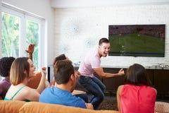 Gruppe Freunde, die auf Sofa Watching Soccer Together sitzen Lizenzfreie Stockfotos