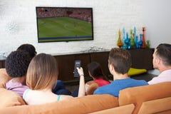 Gruppe Freunde, die auf Sofa Watching Soccer Together sitzen lizenzfreie stockfotografie