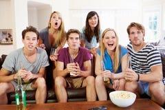 Gruppe Freunde, die auf Sofa Watching Sport Together sitzen Lizenzfreies Stockfoto