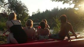 Gruppe Freunde, die in der Natur nach dem Reiten eines Kanus durch den Fluss bei Sonnenuntergang stillstehen stock video