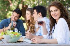 Gruppe Freunde, die draußen essen Stockbild