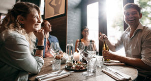 Gruppe Freunde, die ein Abendessen an einem Restaurant genießen lizenzfreie stockfotografie