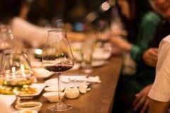 Gruppe Freunde, die ein Abendessen und einen Rotwein essen stockfoto