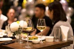 Gruppe Freunde, die ein Abendessen und einen Wein essen lizenzfreie stockfotos