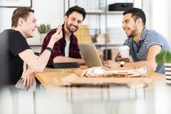 Gruppe Freunde, die ein Zeichen in ein Büro lächeln und betrachten stockbild