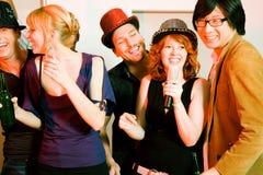 Gruppe Freunde, die eine Karaokeparty haben stockbild