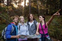 Gruppe Freunde, die eine Karte halten und beim Wandern Vorwärts schauen Stockfoto