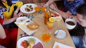 Gruppe Freunde, die in einem Café sitzen Tabelle voll der verschiedenen Nahrung und der Getränke stock footage