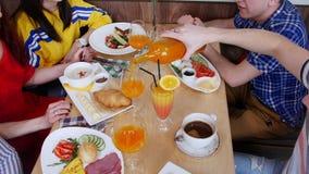 Gruppe Freunde, die in einem Café sitzen Tabelle voll des Lebensmittels und der Getränke stock footage